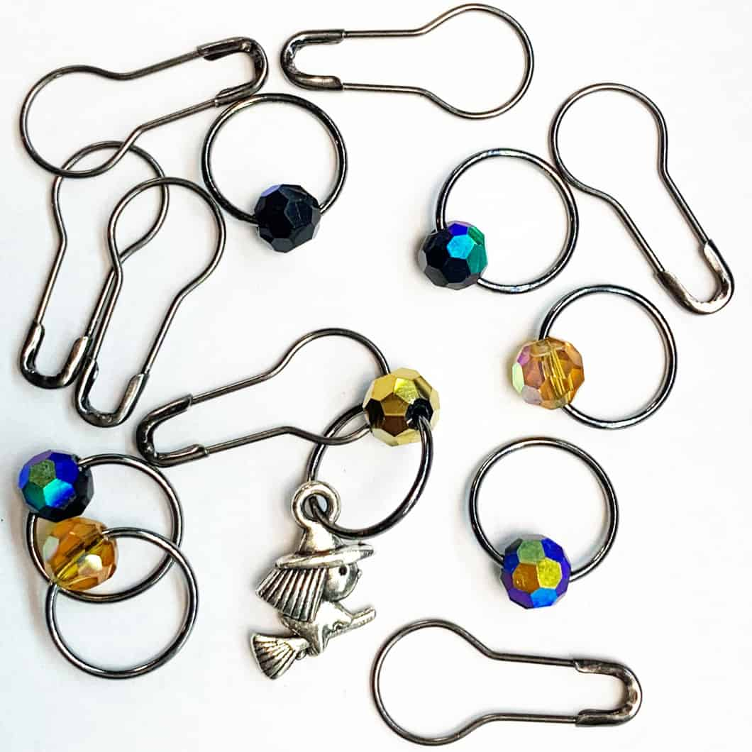 Metal rings with beads of black, blue and gold and a silver witch.