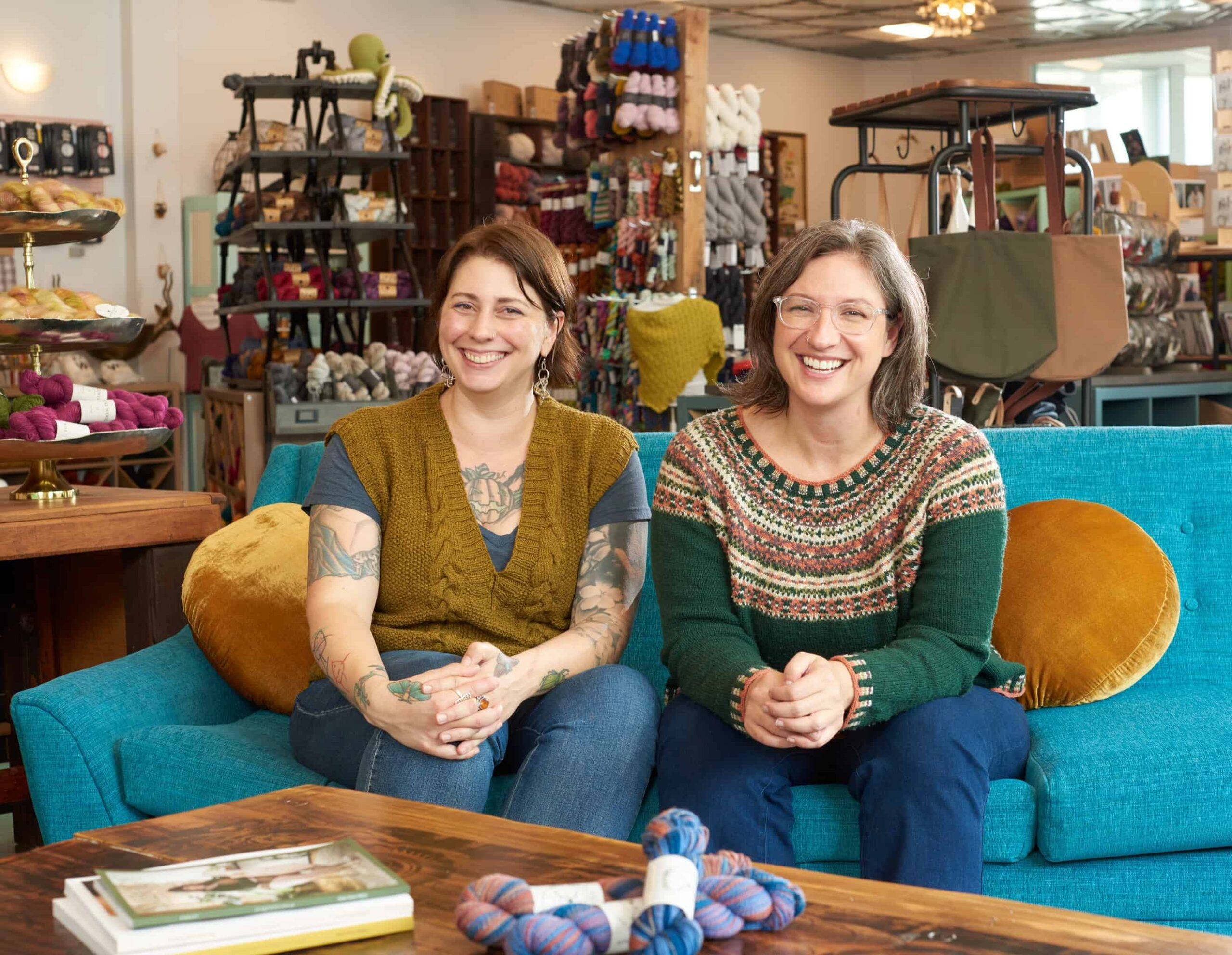 Two light-skinned women wearing sweaters sit smiling on a teal sofa.