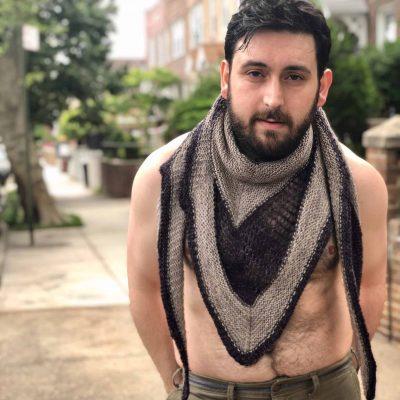 A shirtless man modeling a black and gray shawl.