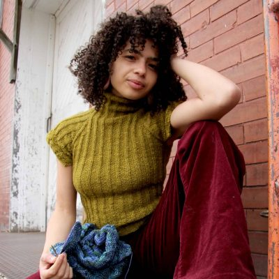 A woman with curly black hair waring a green short-sleeved sweater and red pants, holding a blue knitting project.