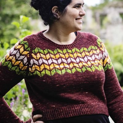 A woman with olive tones skin wearing a maroon sweater with beige, yellow and green colorwork at the chest.