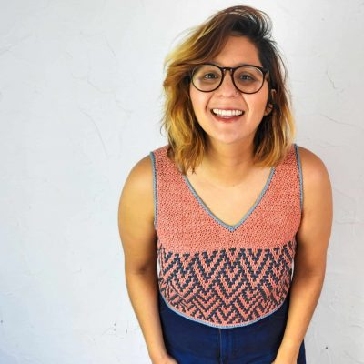 A woman with tan skin, highlighted hair and large glasses wearing a pink and blue crocheted sleeveless top.